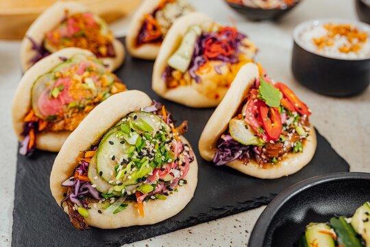 Closeup shot of steamed bao buns on a black surface