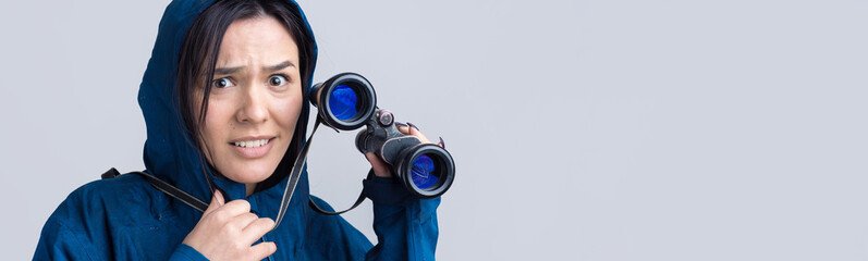 A tourist girl in a blue raincoat holds binoculars in her hands and looks into the distance, spies.