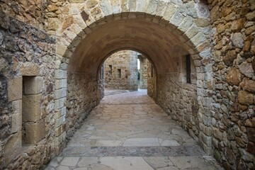 Fototapeta Arch pathway with a cobblestone wall
