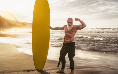 Happy fit senior having fun surfing at sunset time - Sporty bearded man training with surfboard on...