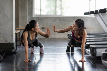Happy women push up and high five in gym
