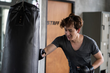 man punch boxing sandbag in fitness gym