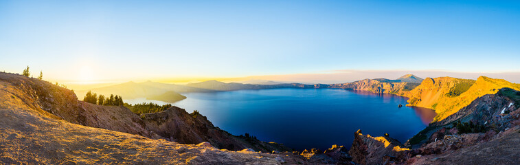 Panorama view of a volcano crater lake at sunset, with forest slopes and still water in a natural park in Oregon, United States
