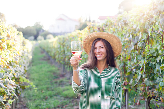 Woman with wineglass of pink wine in vineyard at sunset. Wine tasting in winery. Traveler enjoying local tourism and summer vacation. Happy celebration and social distance. Authentic lifestyle.
