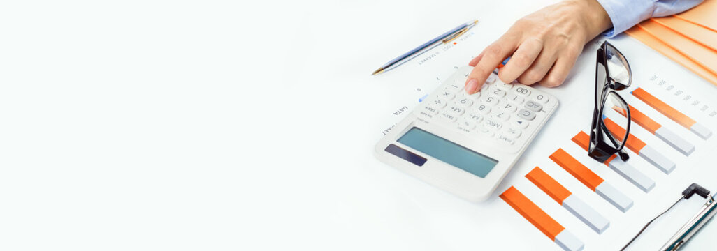 Finance and business concept. Hand with calculator on financial graphs on desk with specs or eyeglasses. Accounting budgeting or market analysis. Home finance. Banner copy space.