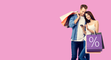 Holiday sales, store mall, retail, consumer concept - happy couple with shopping bags, looking at mobile phone, standing close to each other. Over rose pink color background.