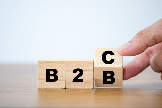 Hand flipping wooden cubes block for change wording B2B to B2C. supply change between Business supplier and customer relations concept.