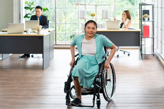 young asian disabled woman with smiling face sitting in the wheelchair and her colleagues sitting next to her in the working office. disability and handicapped concept