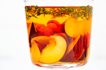 flavored black tea with fresh plums, berries and thyme in glass on white background, closeup
