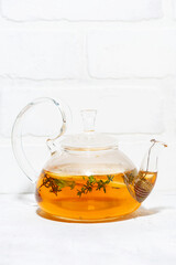 flavored black tea with thyme in a glass teapot, vertical