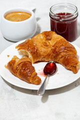 fresh croissant, coffee and strawberry jam, white background, vertical