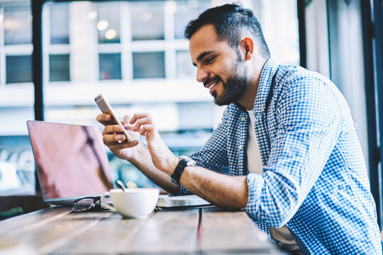 Cheerful male person text messages on smartphone chatting in social networks during coffee break,smiling young man checking mail on cellular pleased with getting discount for mobile internet