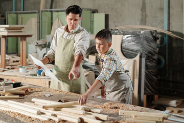 Skilled carpenter in apron pointing at wooden detail while teaching son to make furniture in workshop