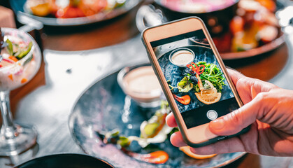 Photo sur Aluminium Inde woman hand with smartphone photographing food at restaurant or cafe