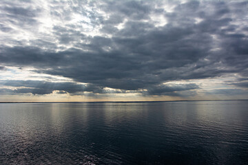 Dark clouds and sun rays in the evening over the Baltic Sea.