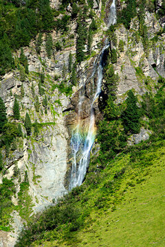 Waterfall in the mountains with rainbow colors.