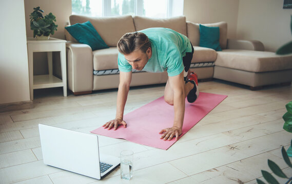 Blonde caucasian man with a laptop is doing fitness out from home on the floor