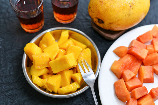 Summer fruits organic papaya and mango with black tea in dark background, Kerala India. Seasonal fruits sweet, healthy and tasty from farms of Munnar.