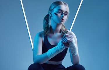 strong beautiful girl with blonde hair, confident look, fists in protective boxing bandages