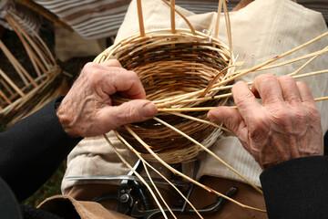 elderly craftsman while weaving a wicker basket
