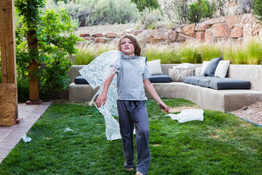 6 year old boy wearing bubble wrap as a cape playing on green lawn with English Cream Golden Retriever