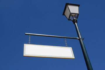 Old fashioned blank sign hanging from a lamp post against blue sky