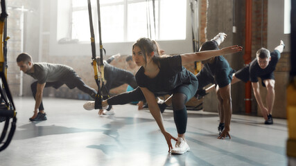 Fly Fitness. Full-length shot of focused caucasian woman doing fitness training exercises at industrial gym. Straps, group workout concept