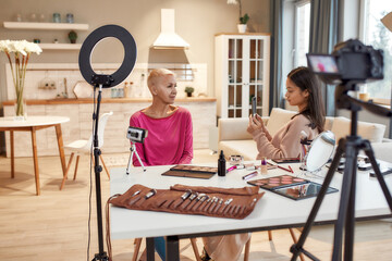 Love the beauty. Asian beauty blogger taking pictures of woman before applying makeup on her face using cosmetic products on the table. Two women recording video for social network