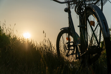 Vintage classic bicycle with nature green backgrounds with water lake river sunset on grass field