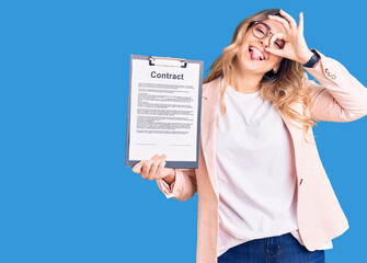 Young caucasian woman holding clipboard with contract document smiling happy doing ok sign with...
