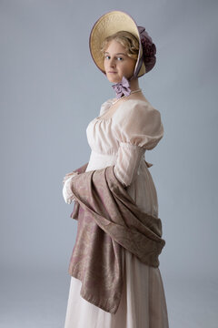 A young Regency period woman in a pale pink gown