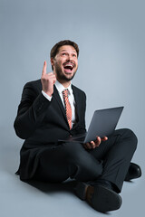 happy businessman with laptop and idea gesture on grey background