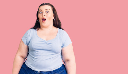 Young plus size woman wearing casual clothes afraid and shocked with surprise expression, fear and...