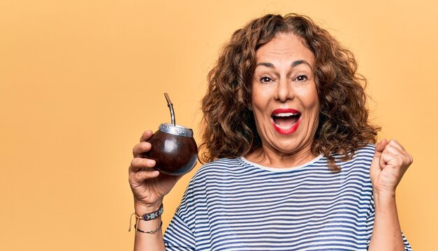 Middle age beautiful woman drinking cup of mate over isolated yellow background screaming proud, celebrating victory and success very excited with raised arm