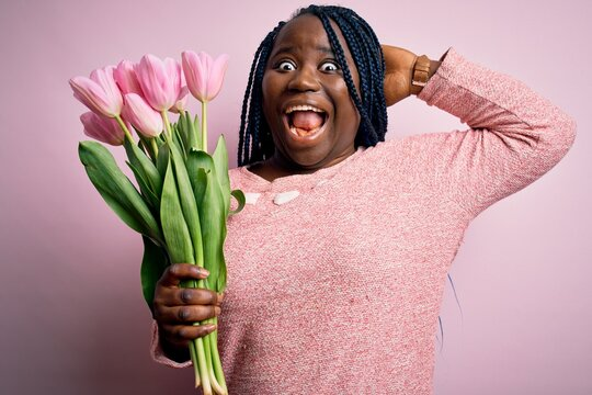 Young african american plus size woman with braids holding bouquet of pink tulips flower Crazy and scared with hands on head, afraid and surprised of shock with open mouth