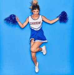 Young beautiful girl wearing cheerleader uniform smiling happy. Jumping with smile on face using...