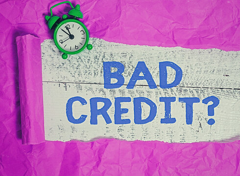 Writing note showing Bad Credit Question. Business concept for a bad credit score due to nonpayment of loans Rolled ripped torn cardboard above a wooden classic table