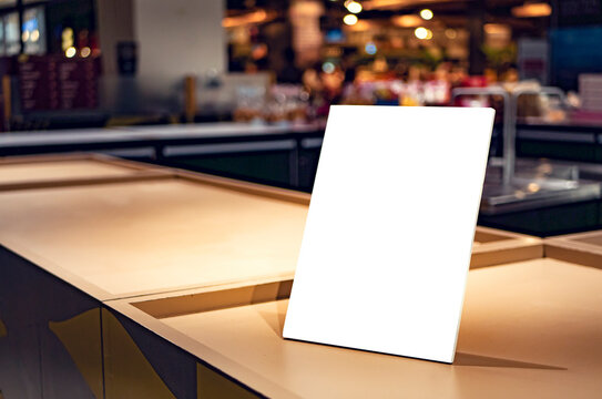 mockup of a food menu list stand on wooden table inside restaurant with people and family sitting having dinner during evening at bar, represent sales promotion and discount design mockup presentation