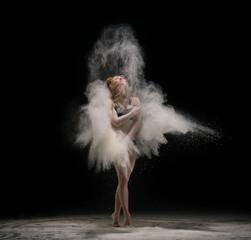 Barefoot woman dancing in cloud of sand