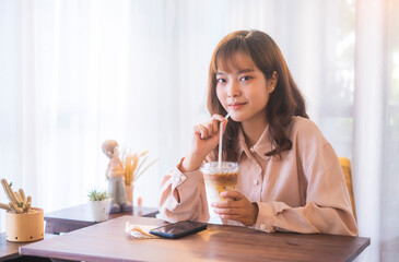 Beautiful Asian girl relaxing thinking casual free time weekend at café drinking coffee social distancing from people friends feeling happy enjoying joyful peaceful cheerful sitting chilling care free
