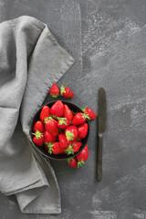 Fresh strawberries in bowl on grey