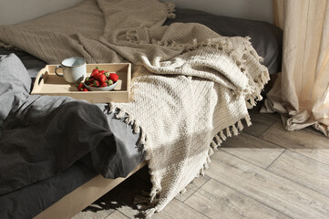 Unmade bed with breakfast at sunlight