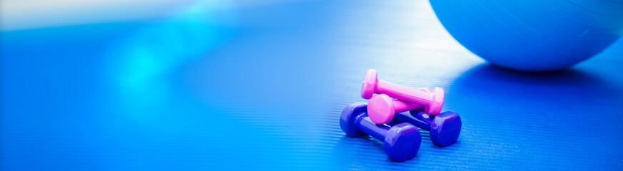 Dumbbells and fitness ball for fitness exercise on blue yoga mat  in fitness or rehabilitation...