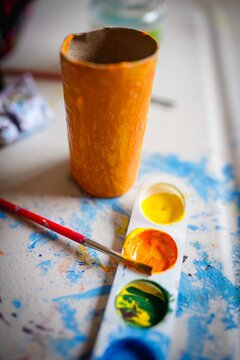 Closeup vertical shot of a small cardboard tube painted in yellow next to the watercolor palette