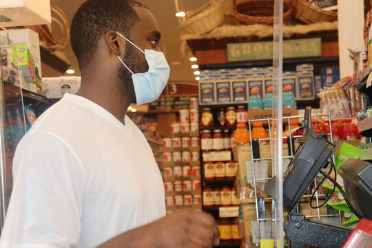 African American man standing in grocery store line wearing blue surgical face mask during Coronavirus pandemic