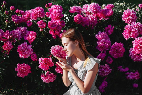 Floral concept. Shallow depth of field.Pink peony flower field.Girl and peonies