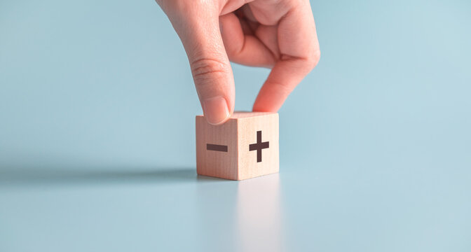 The concept of opposites, hand choose wood blog with plus and minus on blue background, copy space.