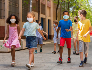 School children in protective medical masks walk along the street of a city
