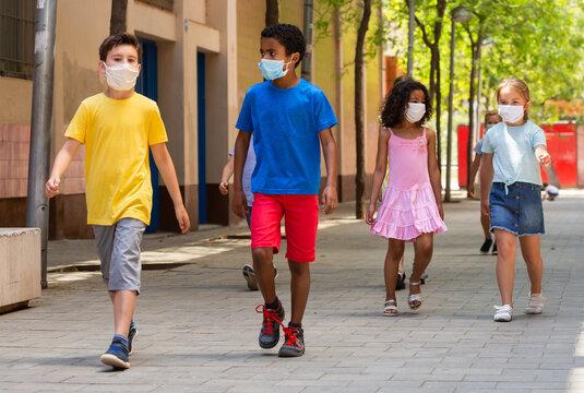 Schoolchildren in masks walking together on the street