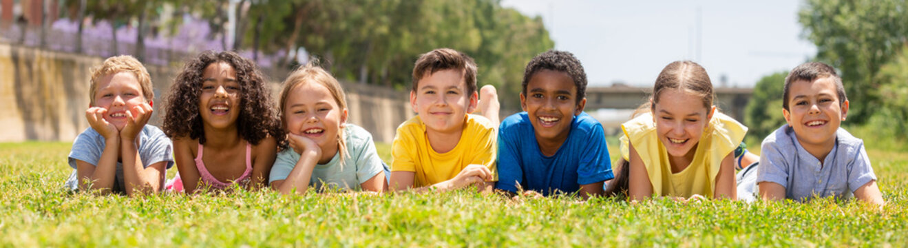 Portrait of smiling children who are posing lying in park